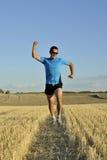 El hombre del deporte que corre al aire libre en el campo de la paja que hace la victoria firma adentro perspectiva frontal fotografía de archivo libre de regalías