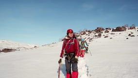 El hombre del escalador se coloca y mira majestuoso la trayectoria viajó por su equipo detrás de él coloca su equipo y nieve amis metrajes