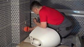 El hombre del fontanero se prepara para la cacerola colgante de la taza del inodoro en nuevo cuarto de baño moderno almacen de video