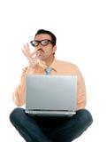 El hombre del friki sienta gesto positivo aceptable del ordenador portátil Foto de archivo