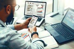 El hombre del inconformista se sienta en café, utiliza smartphone, trabaja en dos ordenadores portátiles con las cartas, gráficos foto de archivo