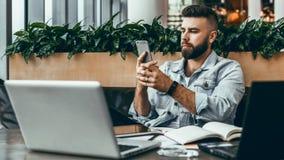 El hombre del inconformista se sienta en café, utiliza smartphone, trabaja en dos ordenadores portátiles El hombre de negocios le foto de archivo