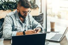 El hombre del inconformista se sienta en café, utiliza smartphone, trabaja en dos ordenadores portátiles El hombre de negocios le imagen de archivo libre de regalías