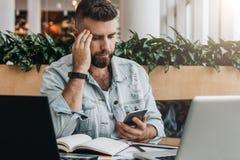 El hombre del inconformista utiliza smartphone, trabaja en dos ordenadores portátiles Los concentrados del hombre de negocios lee fotos de archivo libres de regalías