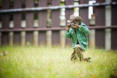 El hombre del juguete toma una figura de acción de la foto fondo del verde Fotografía de archivo