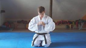 El hombre del karate en kimono se sienta en rodillas en piso en gimnasio de los artes marciales almacen de video
