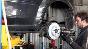 El hombre del mecánico añade el nuevo disco de freno al coche oxidado viejo metrajes