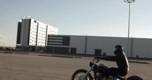 El hombre del motorista monta una moto en el camino en la puesta del sol en ciudad, vista lateral almacen de metraje de vídeo