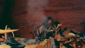 El hombre del Neanderthal lee el libro viejo cerca de hoguera en su cueva almacen de video