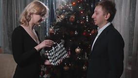 El hombre del novio da la caja rubia del presente de la mujer de la novia con Smartphone cerca del árbol de navidad Familia feliz almacen de metraje de vídeo