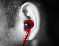 El hombre del oído con un auricular rojo escucha la música Imagen de archivo
