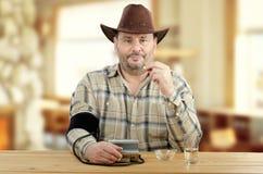 El hombre del país mide la presión arterial antes de tomar píldoras de la prescripción Imagen de archivo