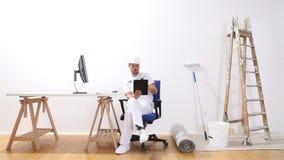El hombre del pintor de casas con el ordenador busca Internet, el comercio electrónico y el concepto de la pintura de la tienda, almacen de metraje de vídeo