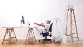 El hombre del pintor de casas con un ordenador ha acabado el trabajo y se relaja, comercio electrónico y los problemas solucionad almacen de video