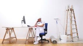 El hombre del pintor de casas con una charla sobre el teléfono, miradas del ordenador en el color muestrea y hace una orden de co almacen de metraje de vídeo