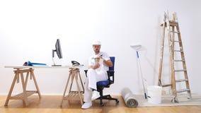 El hombre del pintor de casas con una charla sobre el teléfono, miradas del ordenador en el color muestrea y hace una orden de co almacen de video