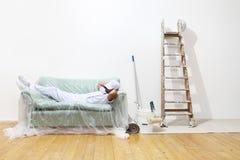 El hombre del pintor en el trabajo, trabajo acabado y se acuesta en el sofá imagen de archivo