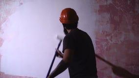El hombre del pintor en el trabajo toma el color con la brocha del rodillo almacen de video
