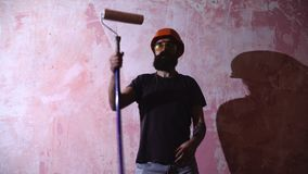 El hombre del pintor en el trabajo toma el color con la brocha del rodillo almacen de metraje de vídeo
