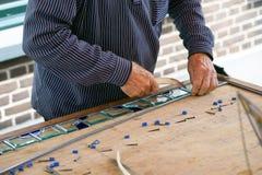 El hombre del pintor hace el vitral imagen de archivo libre de regalías