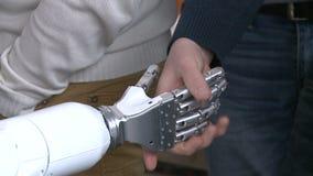 El hombre del primer lleva a cabo y sacude la mano moderna del robot del metal metrajes
