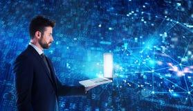 El hombre del programador trabaja con un ordenador portátil en un uso de la red fotos de archivo