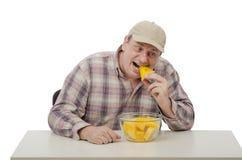 El hombre del pueblo intenta una sandía amarilla Fotografía de archivo