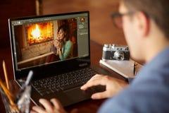 El hombre del retoucher del Freelancer trabaja en el ordenador portátil con la foto que corrige software Fotógrafo o diseñador en fotografía de archivo