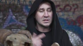 El hombre del retrato en un traje negro con una cabeza cubierta habla y canta mientras que mira la cámara Tirar un clip almacen de metraje de vídeo
