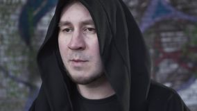 El hombre del retrato en un traje negro con una cabeza cubierta habla y canta mientras que mira la cámara Tirar un clip metrajes