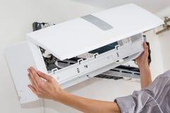 El hombre del servicio es mantenimiento del acondicionador de aire imágenes de archivo libres de regalías