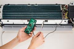 El hombre del servicio es mantenimiento del acondicionador de aire foto de archivo