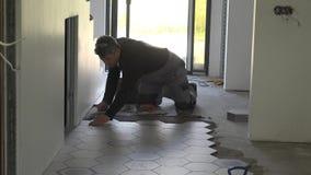 El hombre del solador de la construcción alinea las baldosas en el nuevo acabamiento del apartamento almacen de metraje de vídeo