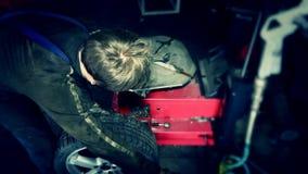 El hombre del trabajador desmonta el neumático de la rueda metrajes