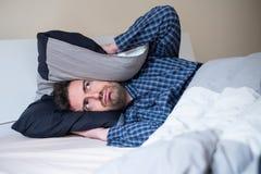 El hombre del trastorno no puede dormir causa del ruido fotos de archivo libres de regalías