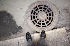 El hombre del Urbanite se coloca cerca de la boca oxidada de la alcantarilla Imagen de archivo libre de regalías
