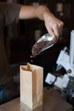 El hombre del vendedor vierte los granos de café en una bolsa de papel Foto de archivo