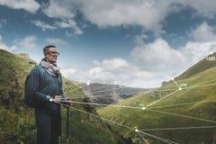 El hombre del viajero con la mochila y postes el emigrar utiliza tecnología aumentada de la realidad en viaje foto de archivo libre de regalías