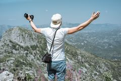 El hombre del viajero en un casquillo y gafas de sol aumentó sus manos para arriba y ve fotografía de archivo