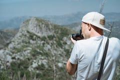 El hombre del viajero en una colocación del casquillo y de las gafas de sol toma una foto con imagenes de archivo