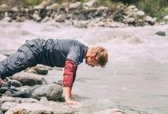 El hombre del viajero se lava la cara con la agua fría en el río de la montaña Foto de archivo libre de regalías