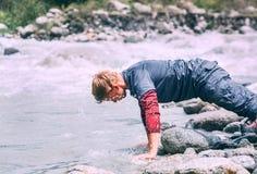 El hombre del viajero se lava la cara con la agua fría en el río de la montaña Imagen de archivo