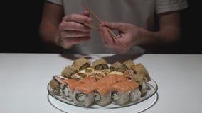 El hombre delante de una placa de los rollos de sushi abre los palillos almacen de metraje de vídeo