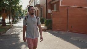 El hombre delgado adulto está caminando solamente en ciudad del verano en d3ia almacen de video