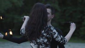 El hombre delgado joven en ropa negra y la mujer atractiva realizan la demostración con la llama al aire libre Demostración exper metrajes