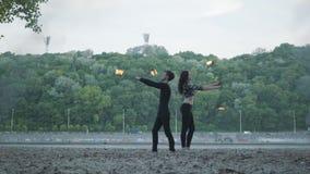 El hombre delgado joven en ropa negra y la mujer atractiva realizan la demostración con la llama al aire libre Demostración exper almacen de video