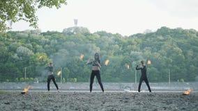 El hombre delgado joven y dos mujeres hermosas realizan simultáneamente la demostración con la llama mientras que se coloca delan metrajes