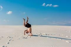 El hombre deportivo joven quiere hacer ejercicios acrobáticos en la arena cerca del río Foto de archivo