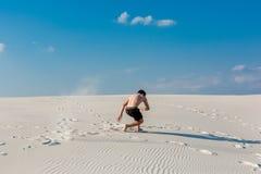 El hombre deportivo joven quiere hacer ejercicios acrobáticos en la arena cerca del río Fotografía de archivo libre de regalías