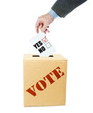 El hombre deposita un papel de votación con sí marcado el checkbox en la caja Fotografía de archivo